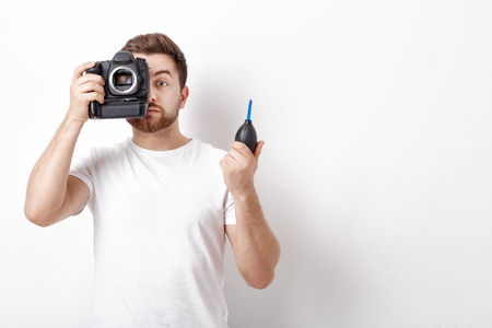 air pressure: photographer cleaning camera with vacuum pump. hand blower dust