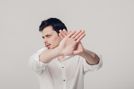 young man with dark hair in white shirt closed with hands on gra Stock Photo