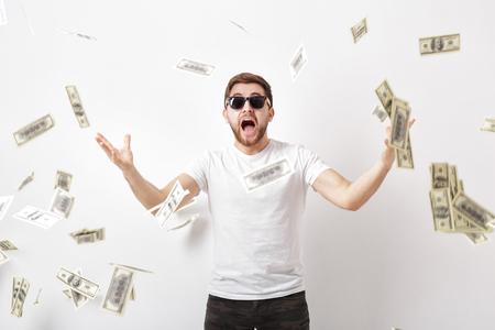 junger glücklicher Mann mit einem Bart im weißen Hemd, das unter Geld steht