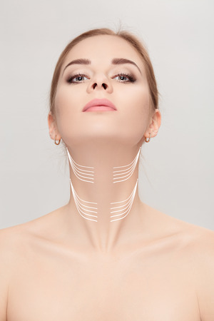woman with arrows on face over grey background. neck lifting con Archivio Fotografico