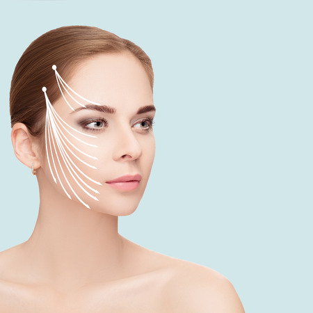 Spa portrait of woman with arrows on her face on blue background Stock Photo - 72372220
