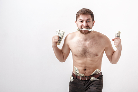 avid: young handsome brunette man with beard eating hundred dollar bill. money and greed Stock Photo