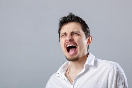白いシャツのグレーの背景があるが叫んで怒っている若い男
