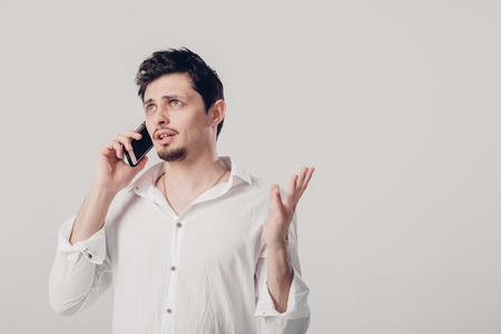 portrait of attractive young brunette man in shirt talking on sm