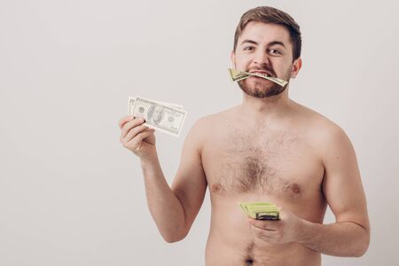 young handsome brunette man with beard eating hundred dollar bill. money and greed Stock Photo
