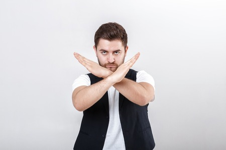 young handsome man with beard in white shirt and black waistcoat shows gesture stop Stock Photo