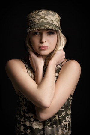 portrait of beautiful woman soldiers in military attire on black background. sadness and despair Stock Photo