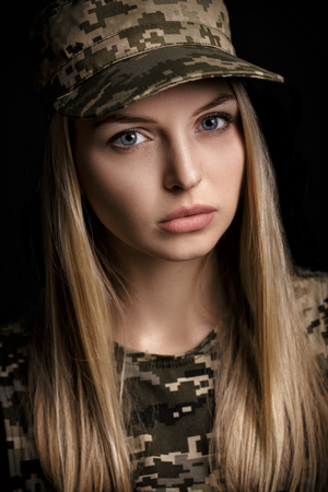 portrait of beautiful woman soldiers in military attire on black background