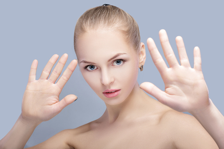 beautiful blond woman protects face with hands on gray background. gesture stop Stock Photo
