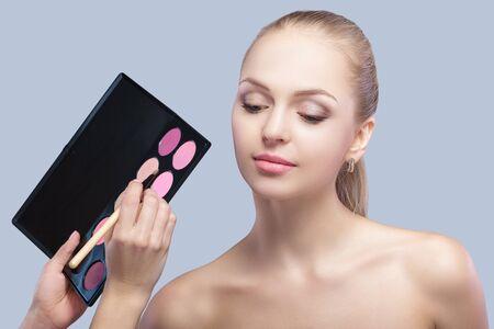 smoky black: makeup artist making eye makeup for beautiful blonde woman . eye shadow
