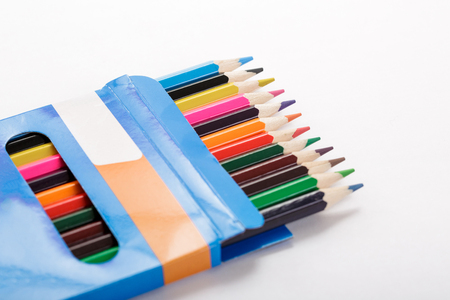 box of colored pencils and sheet of white paper Stock Photo