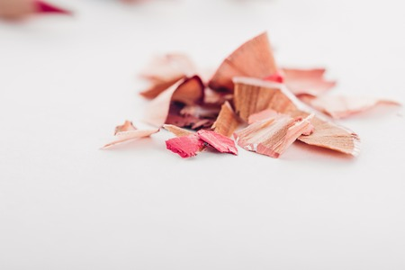 cosmetic pink pencil shavings on white background