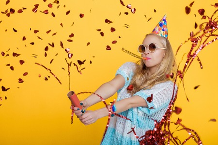 portrait of funny blond woman in birthday hat and red confetti on yellow background. Celebration and party.