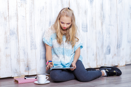 young attractive blond woman is using tablet in front of white wooden wall