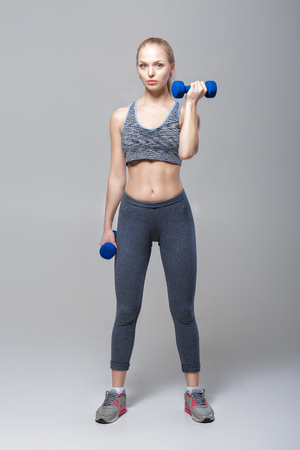 beautiful blonde girl in sportswear does exercises with dumbbells on grey background Stock Photo