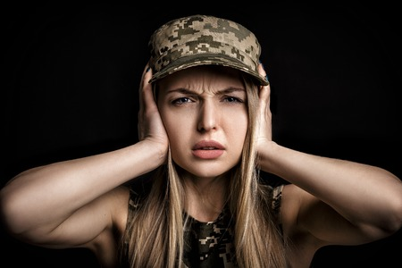portrait of woman soldiers in military attire closes his ears with hands on black background Stock Photo