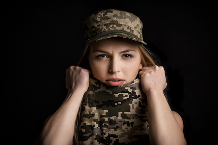 portrait of scared woman soldiers in military attire on black background