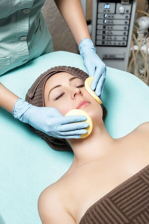 cosmetologist: doctor beautician cleanses skin woman with sponge. cosmetology treatment skincare face. Spa procedures