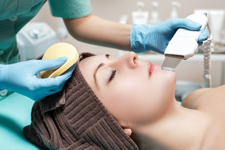 Beautician makes Ultrasonic cleaning of face. cosmetology