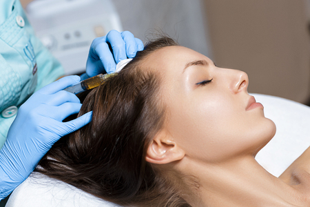 are thrust: Needle mesotherapy. Cosmetic been injected in womans head. Thrust to strengthen hair and their growth Stock Photo