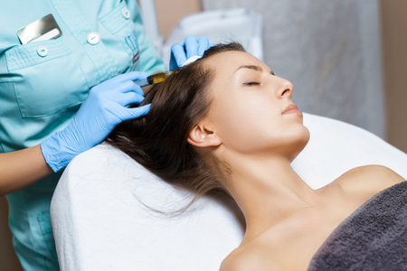 Needle mesotherapy. Cosmetic been injected in womans head. Thrust to strengthen hair and their growth Stock Photo
