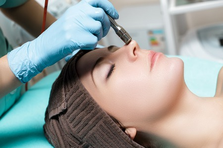 Beautician makes mechanical cleaning of face. Procedure of Microdermabrasion, diamond grinding.