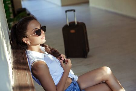 waits: woman with a suitcase sits and waits Stock Photo