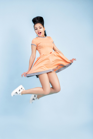 smilling young brunette woman in orange dress jumping on blue background.