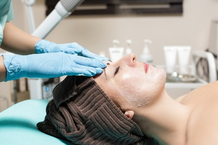 anti-aging facial massage. cosmetologist doing massage for young woman at Spa salon. Stock Photo