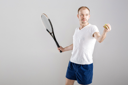 young tennis player plays tennis on grey background Stock Photo