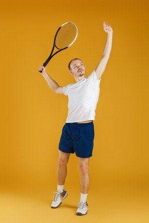 young tennis player plays tennis on yellow background