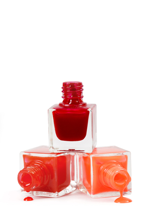 Stack of red nail polish isolated on white background