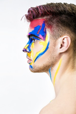 portrait of young attractive man with colored face paint on white background. Professional Makeup Fashion. ffantasy art makeup