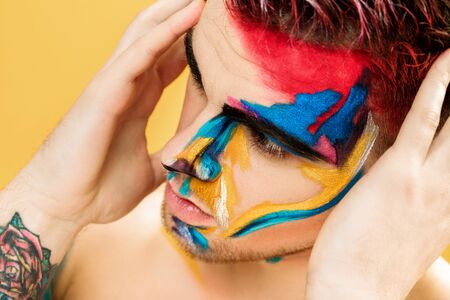 portrait of young attractive man with colored face paint on yellow background. Professional Makeup Fashion. ffantasy art makeup Stock Photo