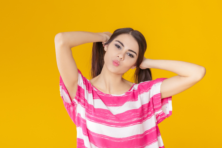 funny young brunette woman fooling around on yellow background. Stock Photo
