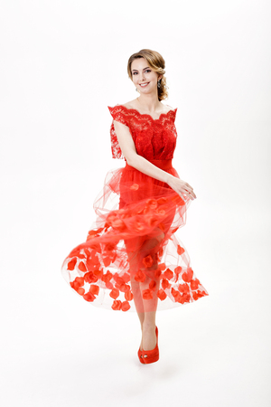 sexy girl dance: attractive young woman in evening red dress on white background Stock Photo