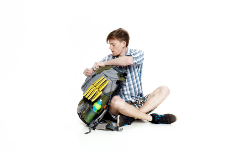 and hiking path: Young tourist is sitting and looking in backpack something on white background. traveler is preparing for hike Stock Photo