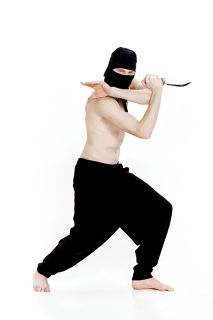 ninja man holds knife and is ready to attack on white background