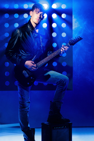 young attractive rock musician playing electric guitar and singing. Rock star on background of spotlights