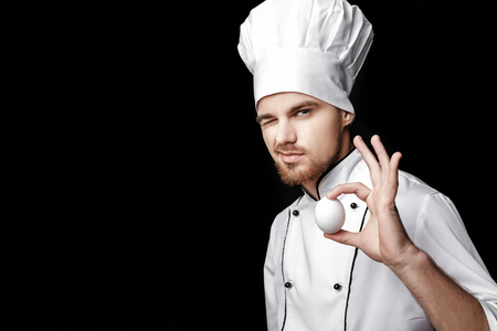 Young bearded man chef In white uniform holds  egg on black background