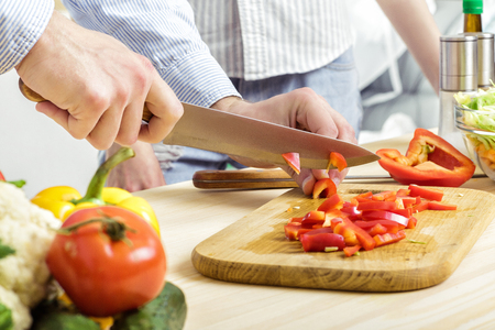 hand bell: Hands of man chopped red bell pepper on board. Couple chopping vegetables in kitchen