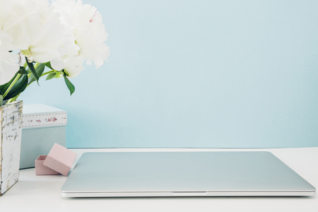 Laptop with white blank screen and flowers in vase on table on blue background. mock up Stockfoto