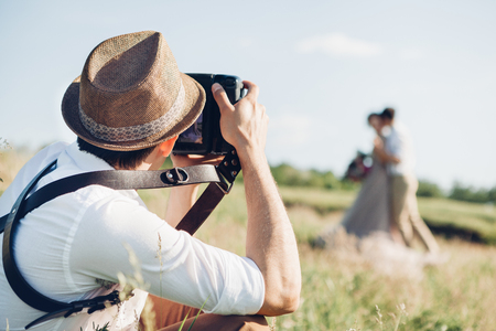 wedding photographer takes pictures of bride and groom in nature, fine art photo Archivio Fotografico