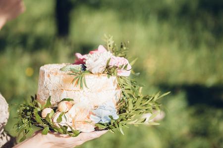 bride holding wedding cake. wedding cake decorated with flowers
