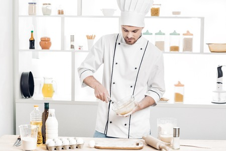 pin board: Chef in uniform makes dough in  kitchen Stock Photo