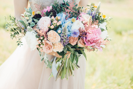 brides hands hold beautiful bridal bouquet of peony. fine art photography. 스톡 콘텐츠