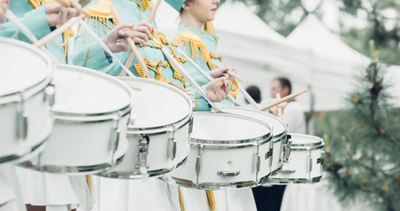 Drummers in green uniform stand in row and drumming