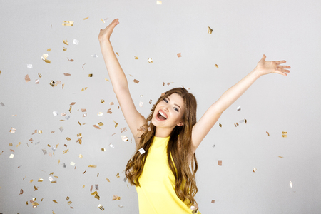 Beautiful happy brunette woman with long hair smiling and confetti falls everywhere. party time Imagens