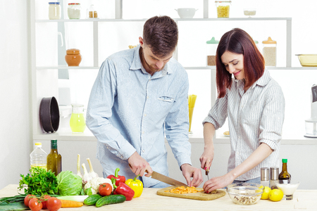 Loving happy couple preparing healthy salad of fresh vegetables in  kitchen