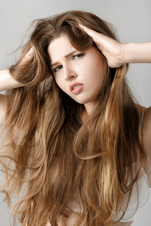 portrait of upset woman with long hair. hopelessness or headache Stock Photo